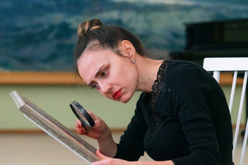 Het meisje bekijkt door een vergrootglas het beeld royalty-vrije stock afbeelding