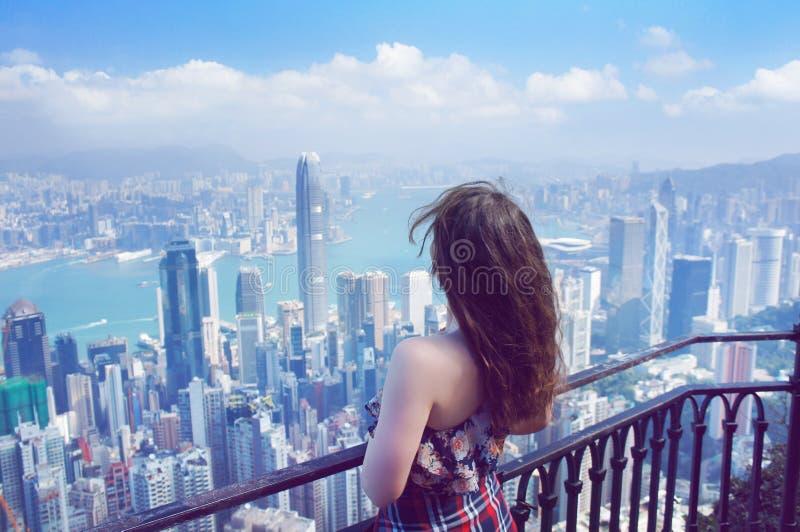 Het meisje bekijkt Hong Kong-gebouwenpanorama van Victoria Peak royalty-vrije stock afbeeldingen