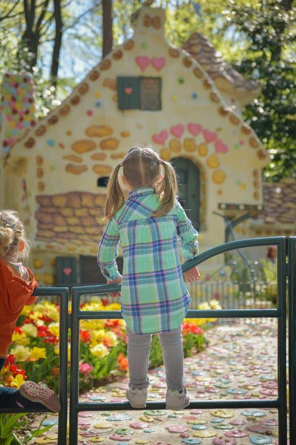 Het meisje bekijkt het huis van de Kleine Rode Berijdende Kap in Efteling-Park in Holland royalty-vrije stock fotografie