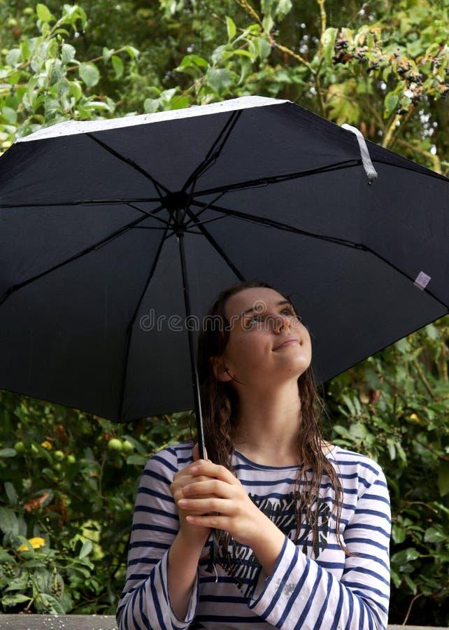 Het meisje bekijkt omhoog haar paraplu stock afbeelding
