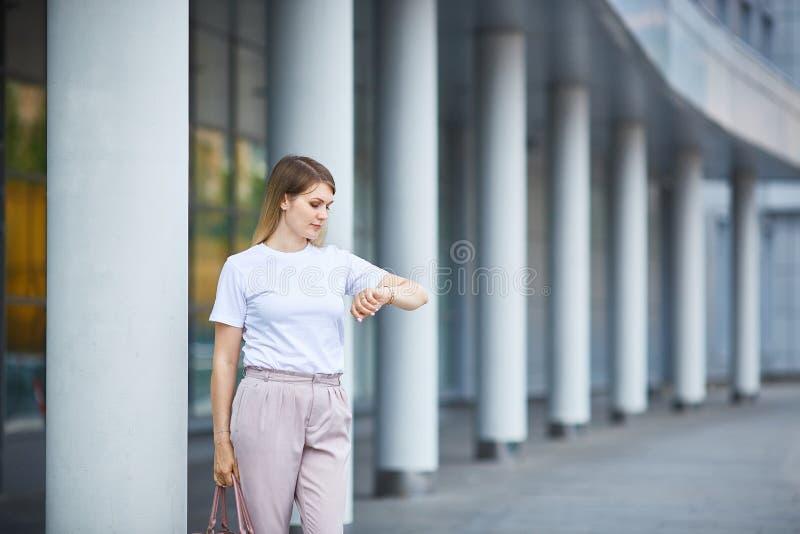 Het meisje bekijkt het polshorloge dichtbij het bedrijfsgebouw stock fotografie