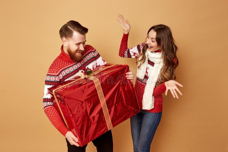 Het meisje bekijkt surprisly de kerel houdend een reusachtige gift Zij allebei zijn gekleed in rode en witte sweaters met herten stock foto