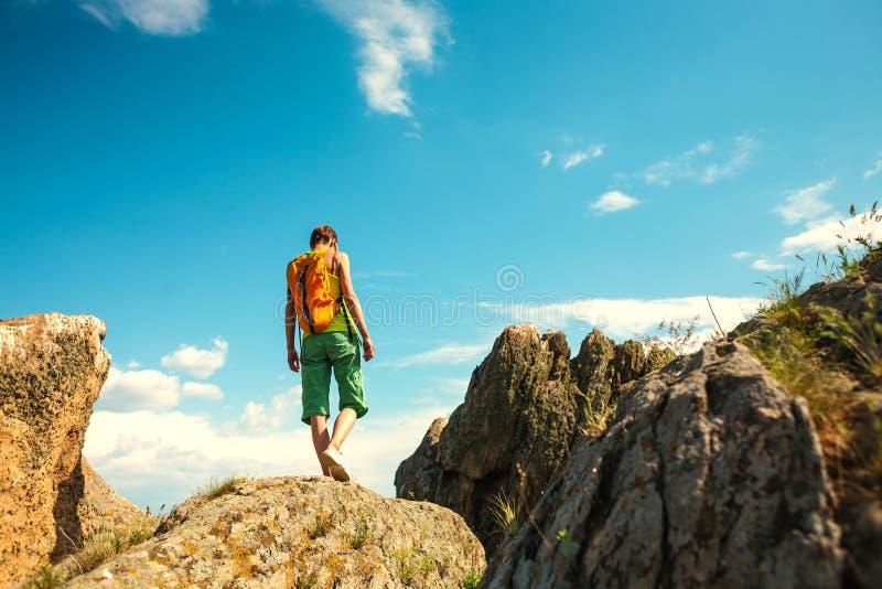 Het meisje beklimt de berg stock afbeelding