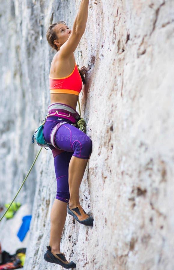 Het meisje beklimt de rots stock foto's