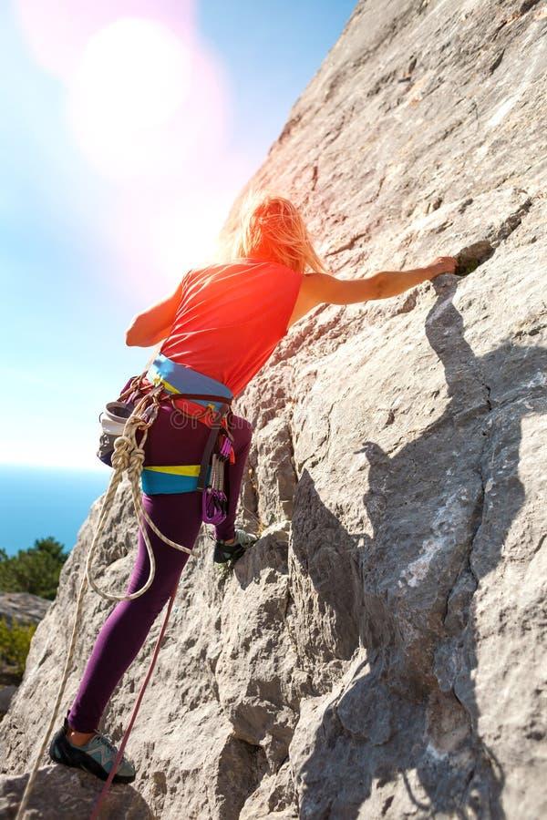 Het meisje beklimt de rots stock foto