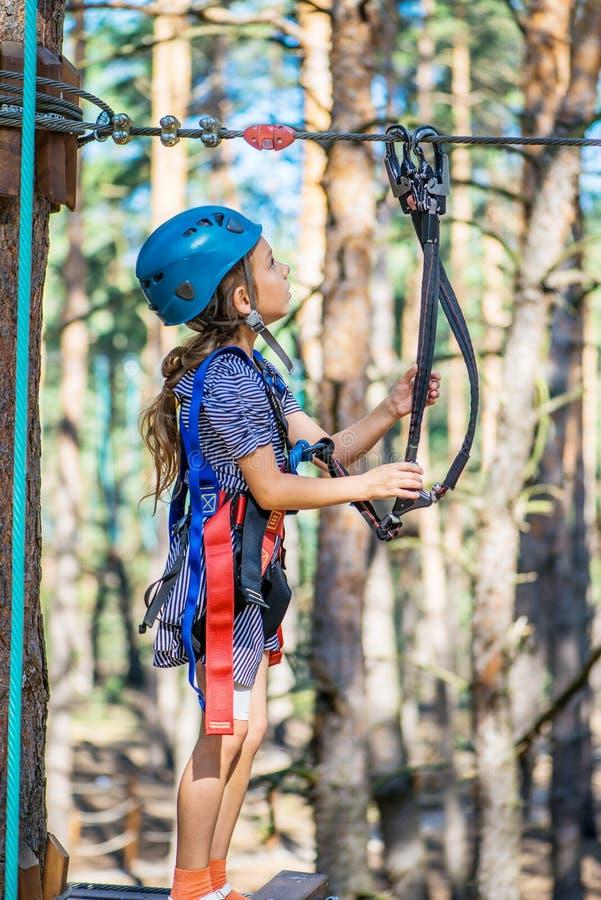 Het meisje beklimt op kabeluitrusting stock afbeelding