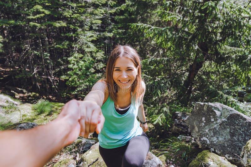 Het meisje beklimt op rots, trekt de partner hand voor hulp terug royalty-vrije stock fotografie