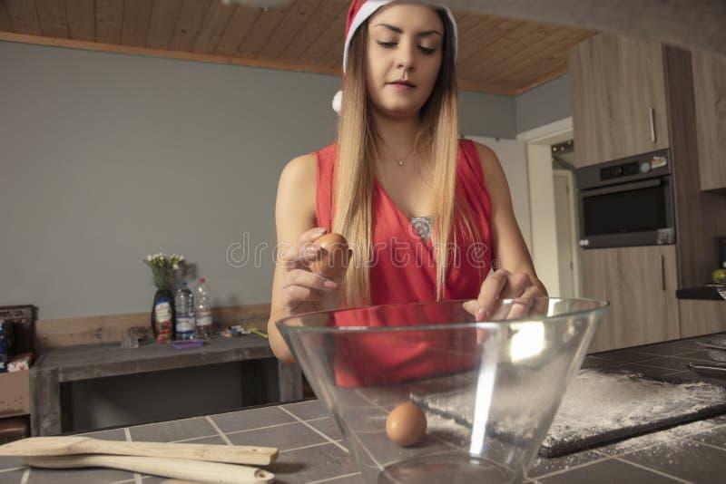 Het meisje bereidt cake op Kerstmis voor, zettend eieren, vooraanzicht stock afbeelding