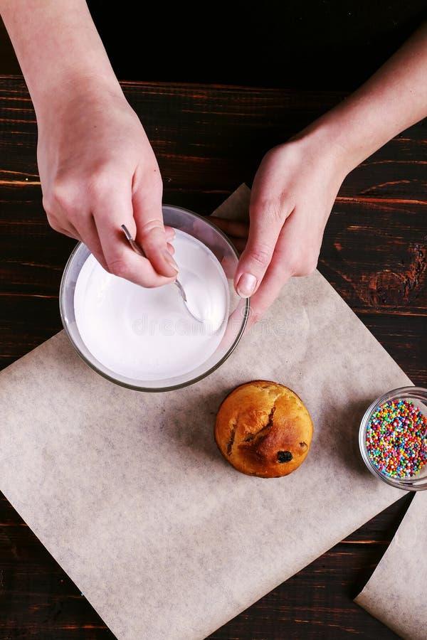 Het meisje bereidt Pasen-baksel voor, smeert de cake met suikerglazuur en bestrooit met gekleurd poeder Het voorbereidingen treff royalty-vrije stock foto