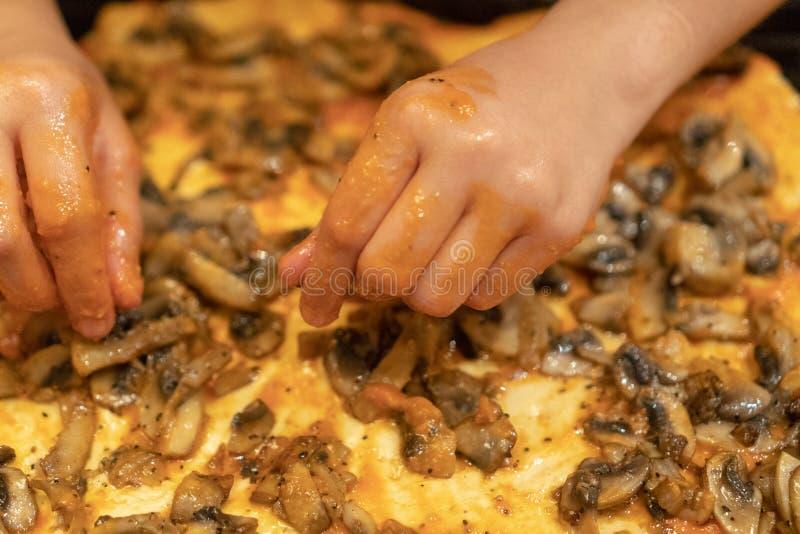 Het meisje bereidt pizza voor Handen van de kind opgemaakte paddestoelen op pizza royalty-vrije stock foto's