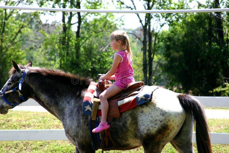 Het meisje berijdt bravely een alleen paard stock fotografie