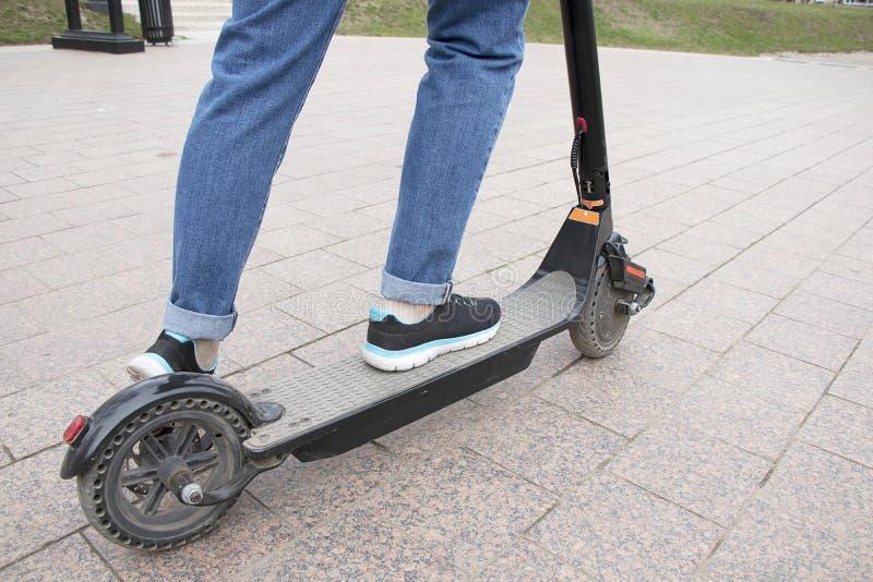 Het meisje berijdt een elektrische autoped in de parkweg, zijaanzicht Technologisch milieuvriendelijk vervoer Moderne actief royalty-vrije stock afbeeldingen