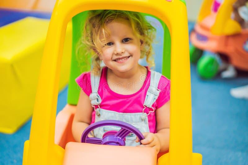 Het meisje berijdt een stuk speelgoed kleurrijke auto stock afbeelding