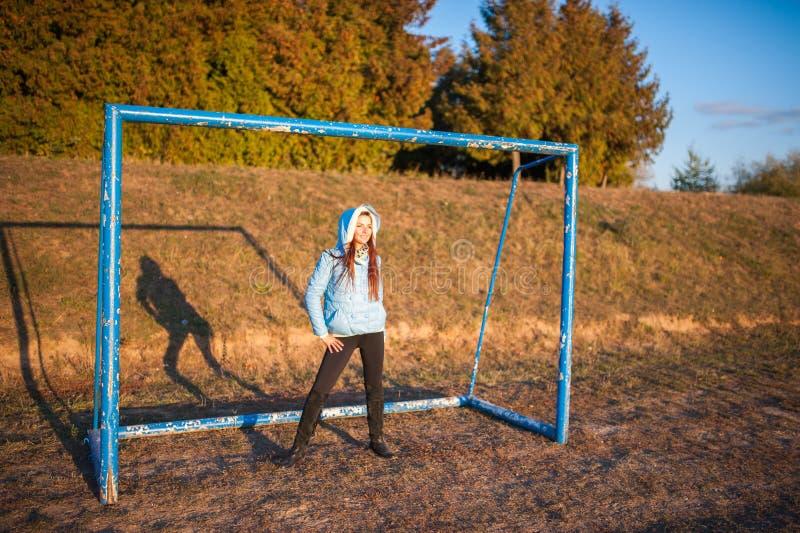Het meisje bevindt zich bij het voetbaldoel donkerbruine meisjestribunes op het doel van voetbal stock foto's