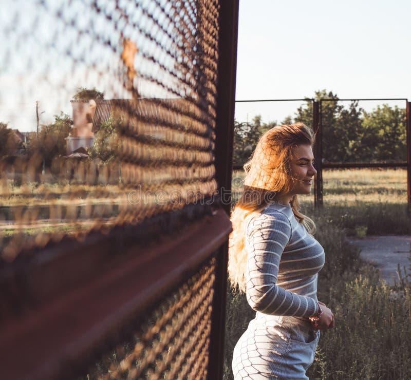 het meisje bevindt zich dichtbij het ijzernet in een grijze blouse en borrels royalty-vrije stock foto's