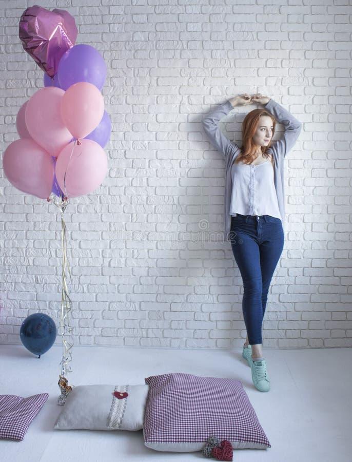 Het meisje bevindt zich dichtbij witte muur met ballons royalty-vrije stock afbeeldingen