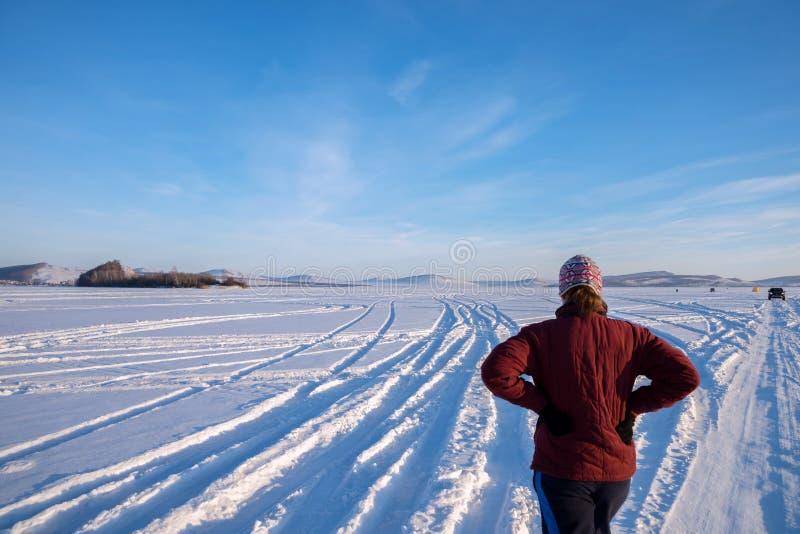 Het meisje bevindt zich op een bevroren meer en bekijkt de vissers op een zonnige de winterdag stock afbeelding
