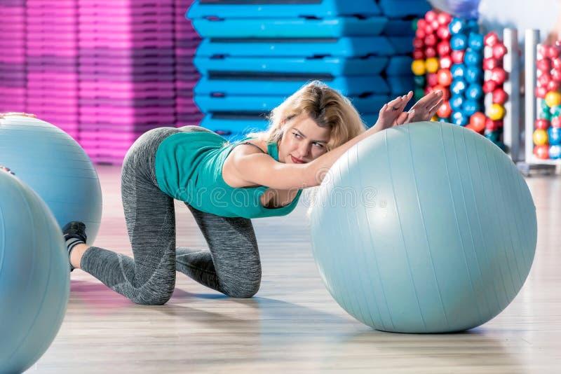 Het meisje is bezet op een gymnastiekbal, bekijkt de trainer, schiet in t stock afbeeldingen