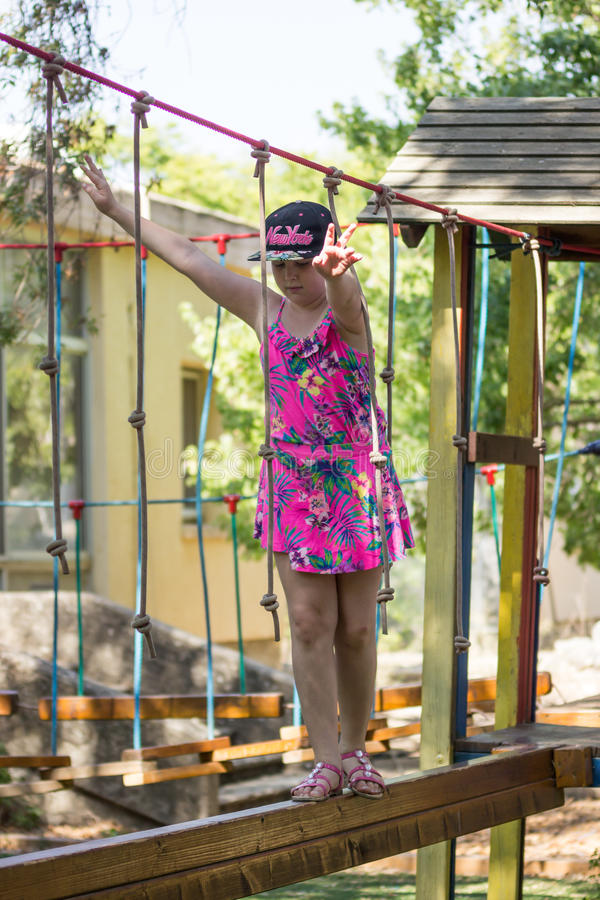 Het meisje is bezig geweest met gymnastiek op speelplaats stock foto