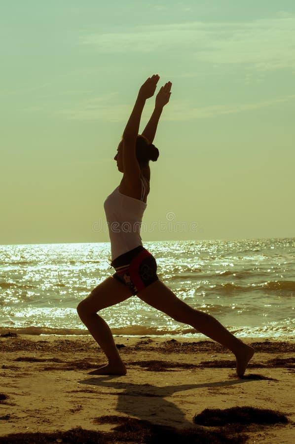 Het meisje is bezig geweest met yoga op het strand stock afbeeldingen