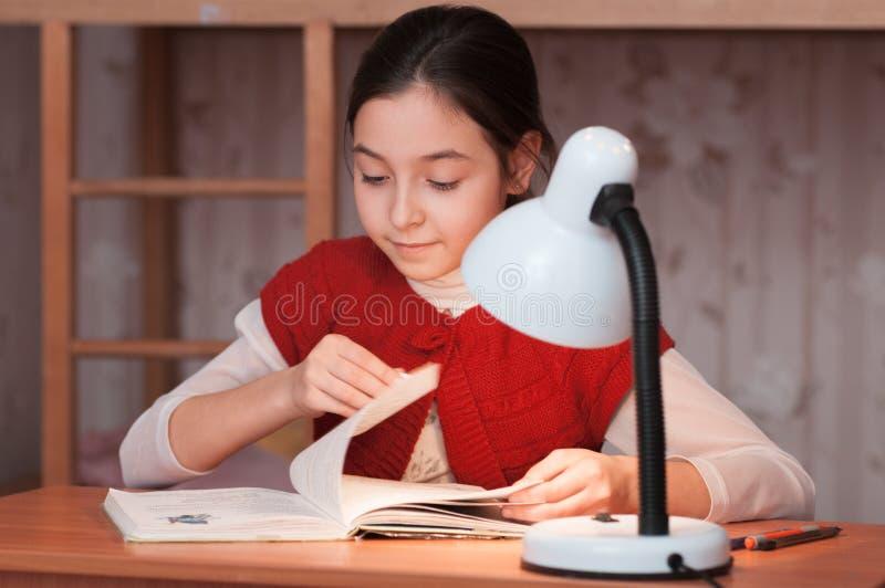 Meisje die bij bureau een boek lezen door licht van de lamp stock afbeelding