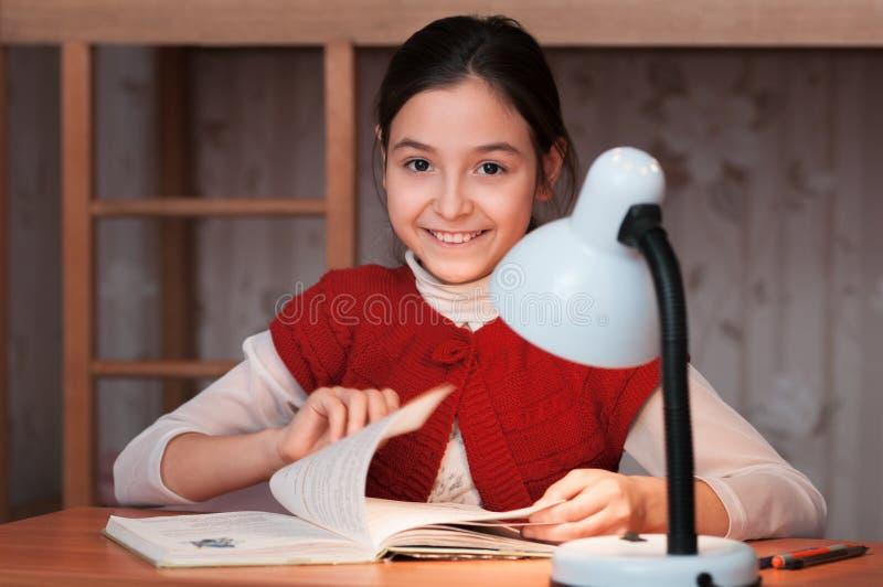 Meisje die bij bureau een boek lezen door licht van de lamp royalty-vrije stock afbeeldingen