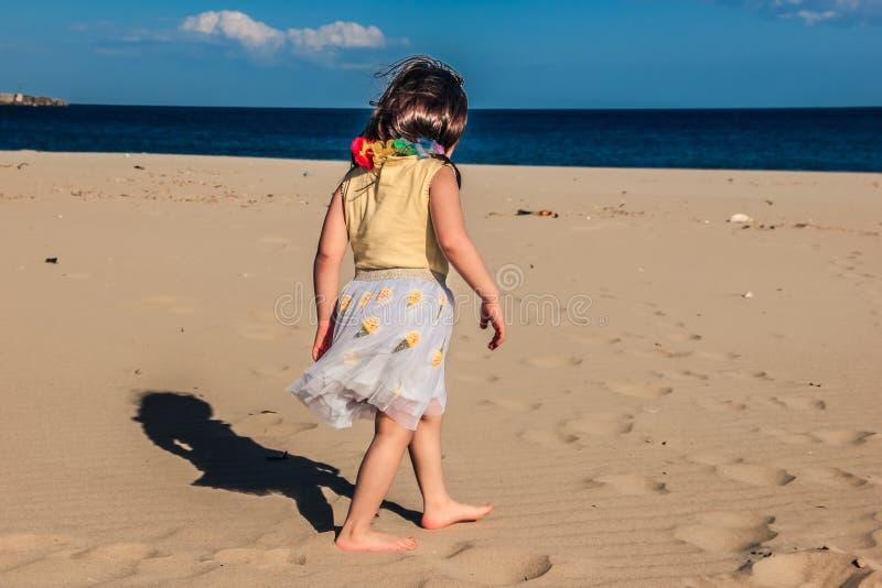 Het meisje bij strand, de zomer kleedde de gangen van het kindmeisje op zand voor shells royalty-vrije stock afbeelding