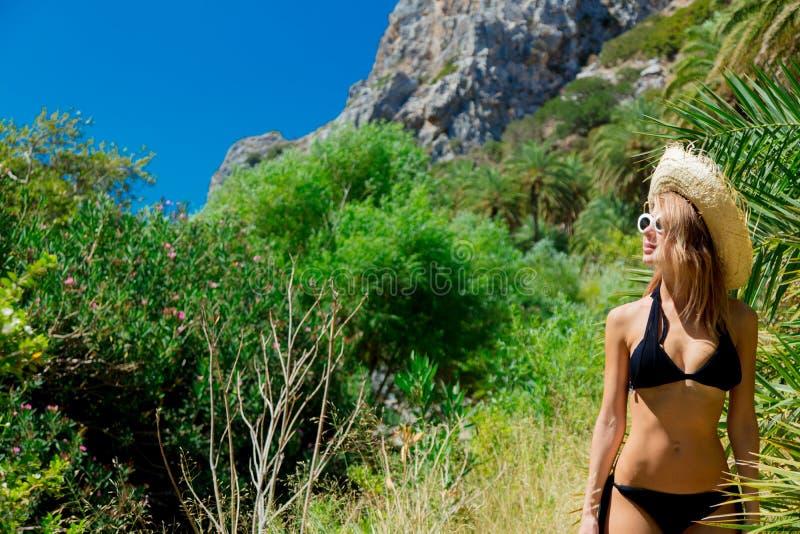 Het meisje in bikini en de hoed hebben rust in palmbos stock foto's
