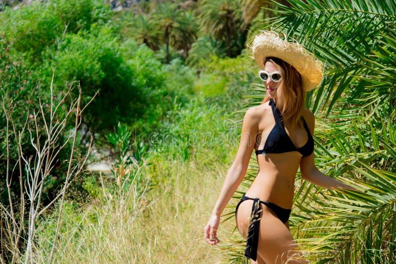 Het meisje in bikini en de hoed hebben rust in palmbos stock fotografie