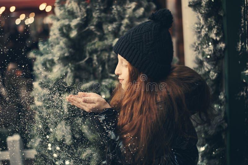 Het meisje blaast sneeuw van haar handen op een sneeuwvlokken bokeh achtergrond stock foto
