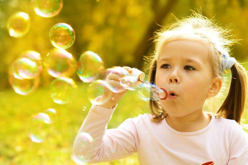 Het meisje blaast zeepbels stock afbeeldingen