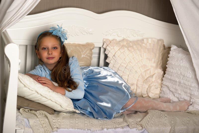 Het meisje in blauw op de bank stock afbeeldingen
