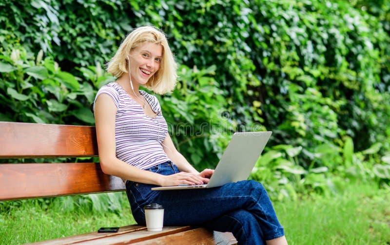 Het meisje blogger schrijft post voor sociaal netwerk moderne vrouw met notitieboekje openlucht blogging de zomer online Vrouwend stock afbeelding