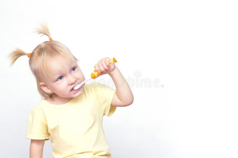 Het meisje het blonde met vlechten op het hoofd van de Kaukasische verschijning borstelt haar tanden en kijkt weg witte achtergro royalty-vrije stock afbeelding
