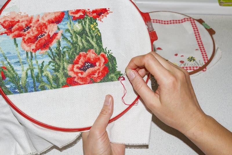Het meisje borduurt dicht omhoog beeld Handen, naald, draad en borduurwerk Hobbyhuis met eigen handen Met de hand gemaakte produc stock afbeelding