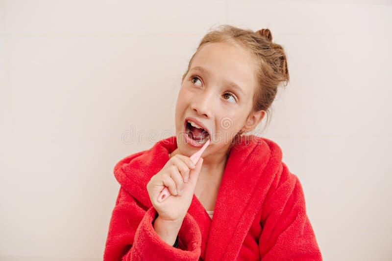 Het meisje borstelt tanden in een badkamers stock afbeeldingen