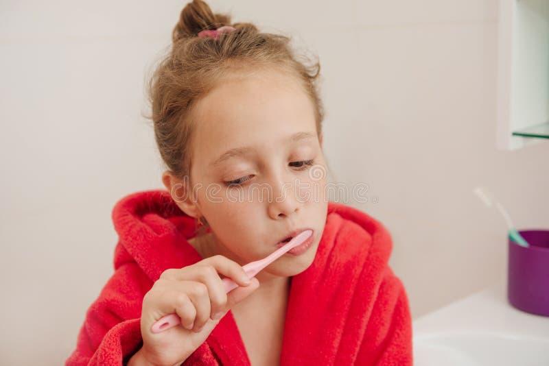 Het meisje borstelt tanden in een badkamers in een rode peignoir stock foto