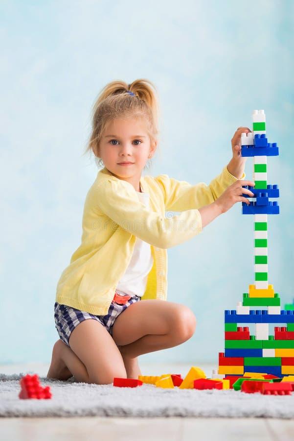 Het meisje bouwde een toren van kubussen De vreugde van spelen stock afbeeldingen