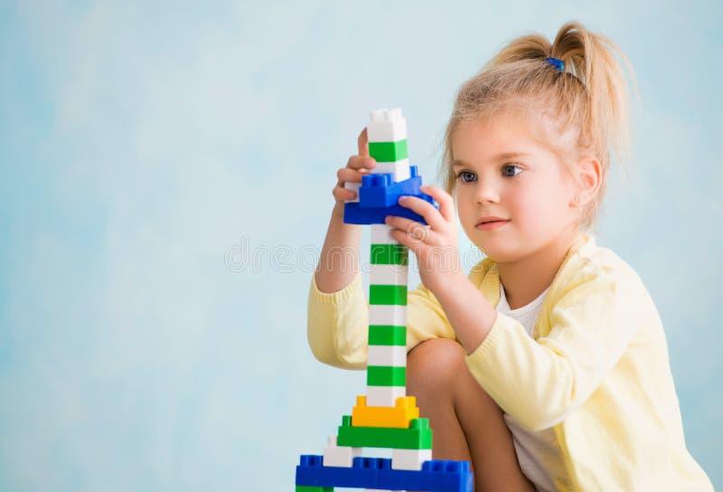 Het meisje bouwde een toren van kubussen De vreugde van spelen royalty-vrije stock foto's