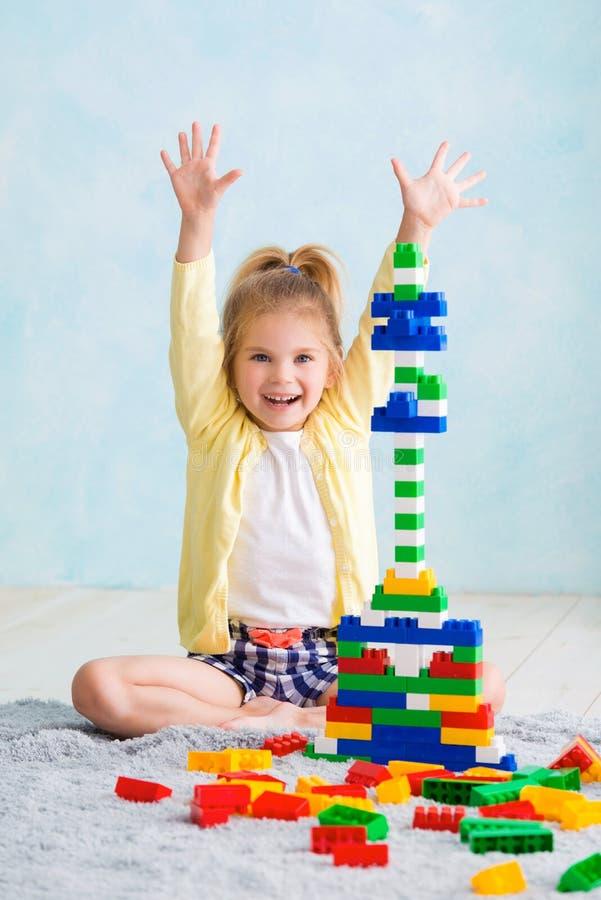 Het meisje bouwde een toren van kubussen De vreugde van spelen royalty-vrije stock afbeeldingen