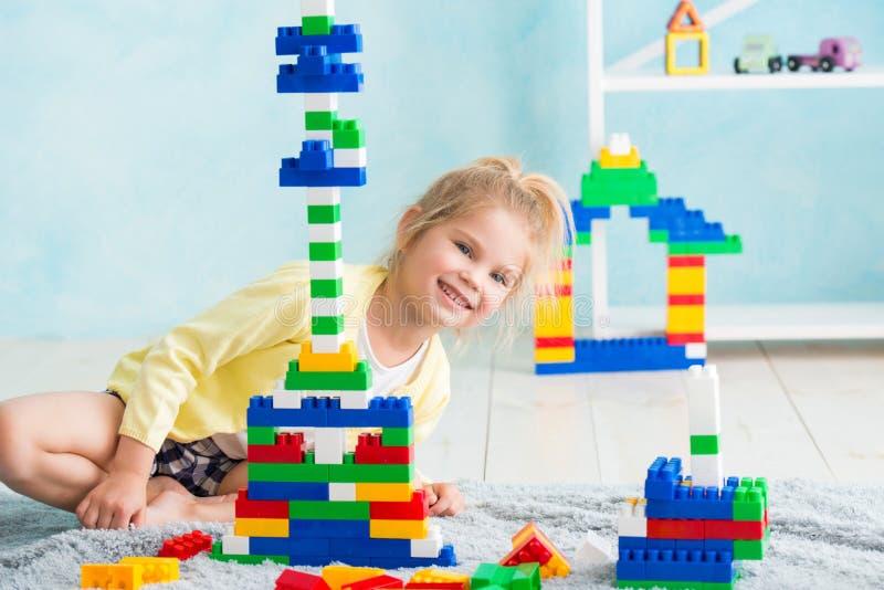 Het meisje bouwde een toren van kubussen De vreugde van spelen royalty-vrije stock afbeelding