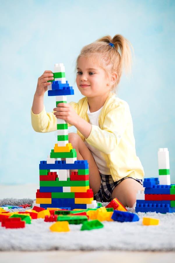 Het meisje bouwde een toren van kubussen De vreugde van spelen royalty-vrije stock foto