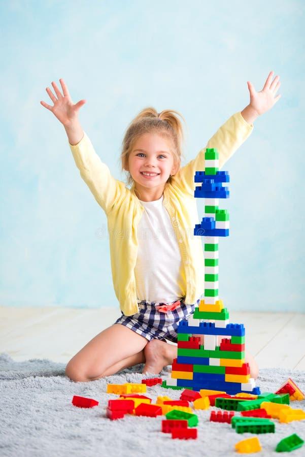 Het meisje bouwde een toren van kubussen De vreugde van spelen stock foto