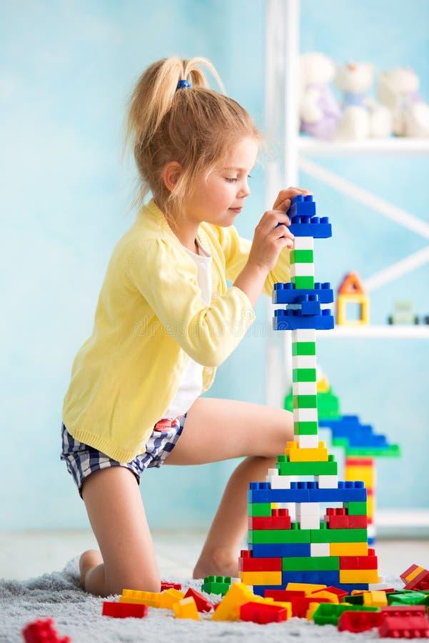 Het meisje bouwde een toren van kubussen De vreugde van spelen stock fotografie