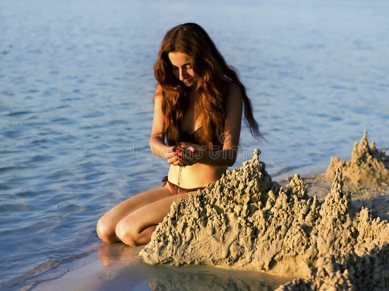 Het meisje bouwt een zandkasteel op het strand stock foto's