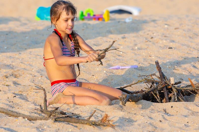 Het meisje breekt kreupelhout voor een vuur op een zandig strand stock afbeeldingen