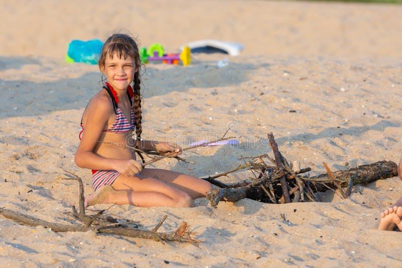 Het meisje breekt kreupelhout voor een vuur op een zandig strand en onderzocht het kader stock fotografie