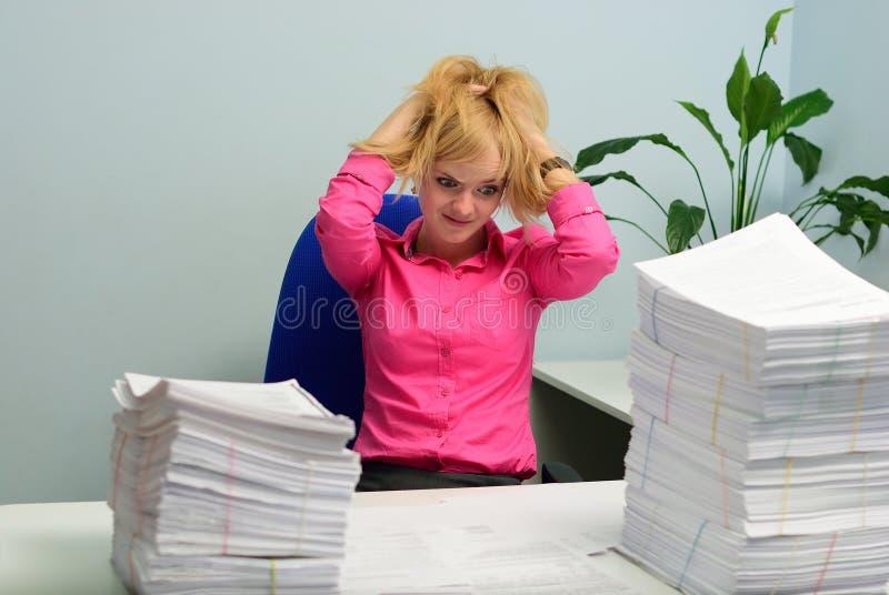 Het meisje in het bureau bekijkt met verschrikking de stapel van documen stock foto