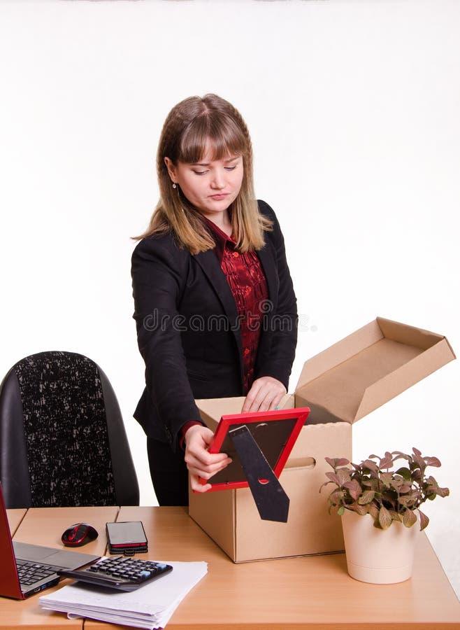 Het meisje in bureau verzamelt, ontleedt persoonlijke bezittingen een doos royalty-vrije stock afbeeldingen