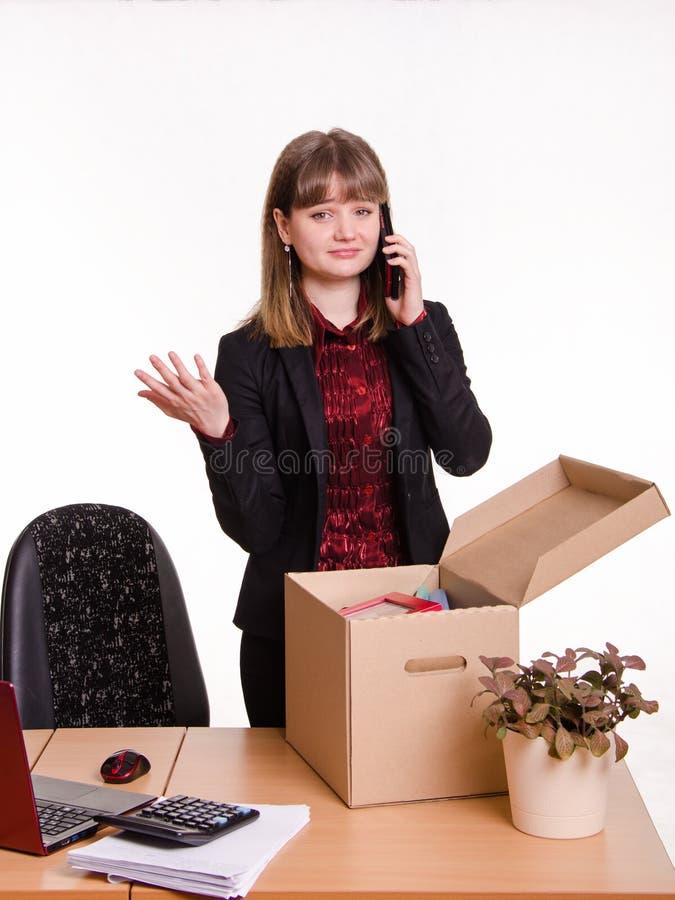 Het meisje in bureau verzamelt persoonlijke bezittingen en het uitnodigen van telefoon stock afbeelding